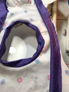 Neckband sewn in the round, shoulder band partially attached.